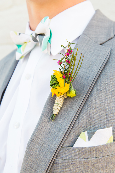 Boutonniere-style-heather-grey-notch-lapel-suit-with-a-colorful-bow-tie-and-yellow-floral-boutonniere