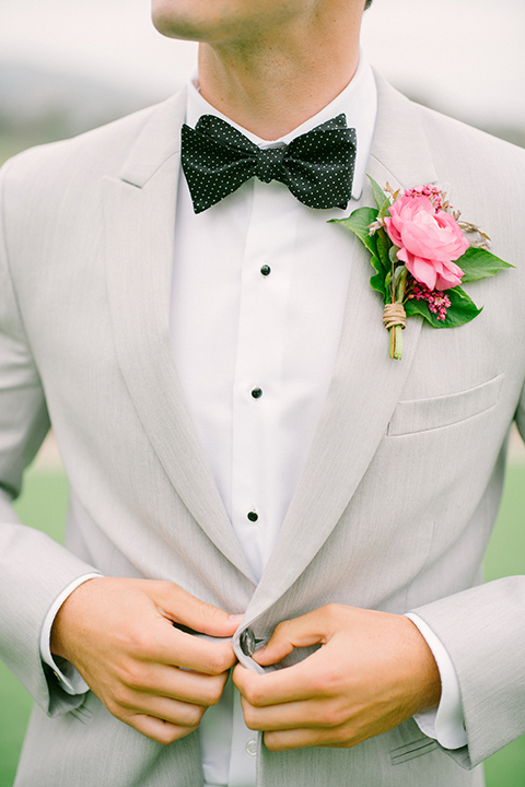 Boutonniere-style-light-grey-peak-lapel-suit-with-a-black-bow-tie-and-pink-floral-boutonniere