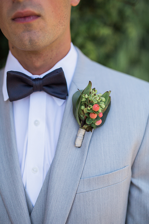 boutonniere style light grey peak lapel suit with a charcoal grey bow tie and a green boutonniere