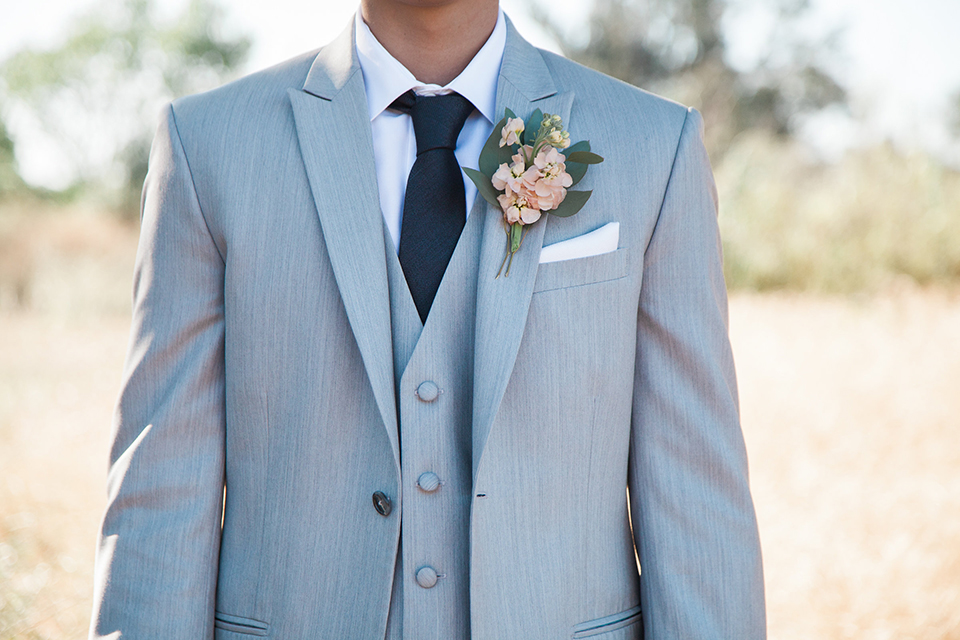 Boutonniere-style-light-grey-peak-lapel-suit-with-a-navy-long-tie-and-light-pink-floral-boutonniere