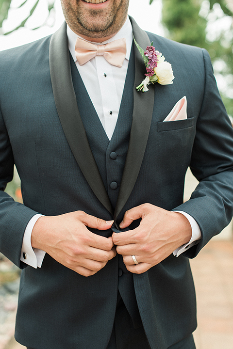 Boutonniere-style-navy-shawl-lapel-tuxedo-with-a-blush-pink-bow-tie-and-white-and-red-floral-boutonniere