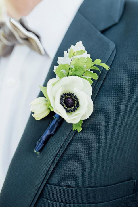 Boutonniere-style-slate-blue-notch-lapel-suit-with-a-grey-pipe-edge-bow-tie-and-simple-white-floral-boutonniere