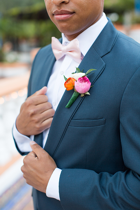 Boutonniere-style-slate-blue-notch-lapel-suit-with-a-matching-bow-tie-and-pink-floral-boutonniere