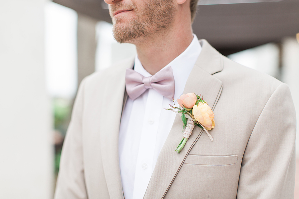 Boutonniere-style-tan-notch-lapel-suit-with-a-blush-pink-bow-tie-and-light-yellow-and-orange-floral-boutonniere