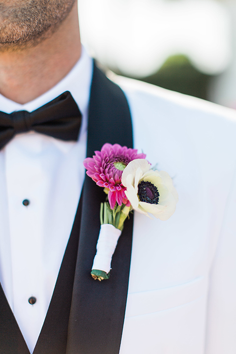 Boutonniere-style-white-shawl-lapel-tuxedo-with-a-black-bow-tie-and-white-and-pink-floral-boutonniere