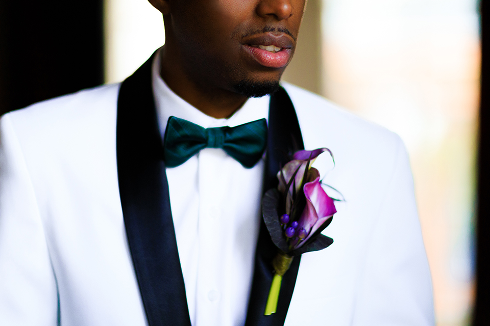 Boutonniere-style-white-shawl-lapel-tuxedo-with-a-dark-green-bow-tie-and-a-big-purple-floral-boutonniere