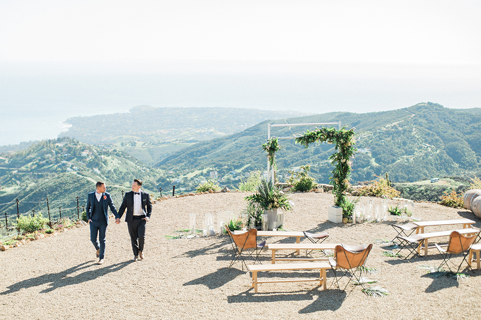 Los angeles same sex outdoor wedding at malibu solstice canyon groom navy shawl lapel tuxedo with a white dress shirt and black and white dot bow tie with groom blue notch lapel suit with a white dress shirt and white bow tie and orange floral boutonniere holding hands and walking by ceremony set up
