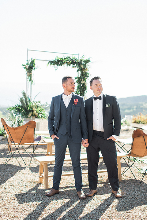 Los angeles same sex outdoor wedding at malibu solstice canyon groom navy shawl lapel tuxedo with a white dress shirt and black and white dot bow tie with groom blue notch lapel suit with a white dress shirt and white bow tie and orange floral boutonniere standing by ceremony set up holding hands