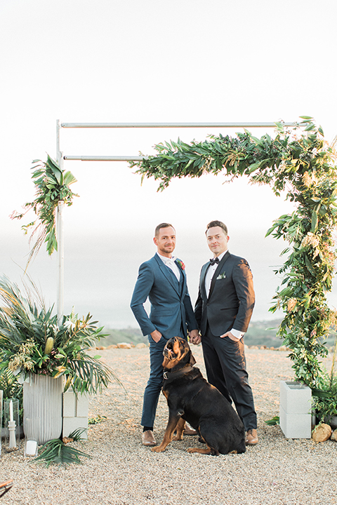 Los angeles same sex outdoor wedding at malibu solstice canyon groom navy shawl lapel tuxedo with a white dress shirt and black and white dot bow tie with groom blue notch lapel suit with a white dress shirt and white bow tie and orange floral boutonniere hugging and holding hands standing with dog at ceremony set up
