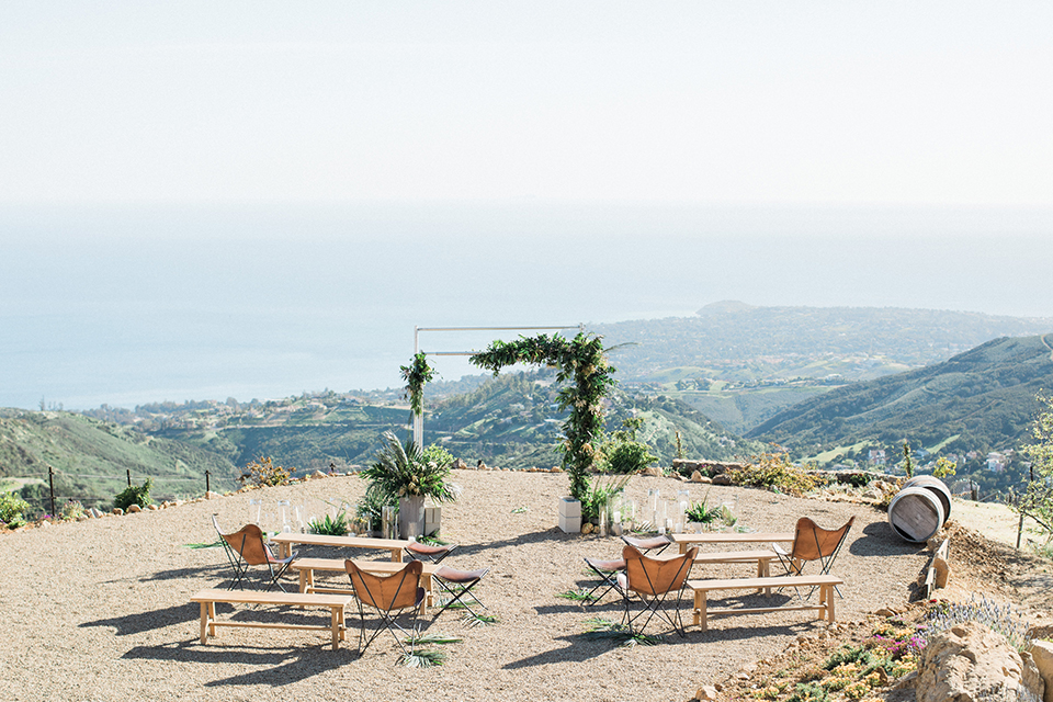 Los angeles outdoor same sex wedding at malibu solstice canyon ceremony set up with brown chairs and benches with a greenery altar and greenery florals along aisle wedding photo idea for ceremony set up