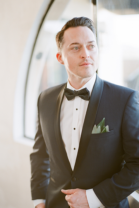 Los angeles same sex outdoor wedding at malibu solstice canyon groom navy shawl lapel tuxedo with a white dress shirt and black and white dot bow tie with greenery pocket boutonniere
