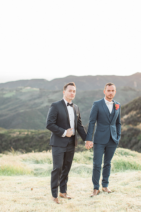 Los angeles same sex outdoor wedding at malibu solstice canyon groom navy shawl lapel tuxedo with a white dress shirt and black and white dot bow tie with groom blue notch lapel suit with a white dress shirt and white bow tie and orange floral boutonniere holding hands standing