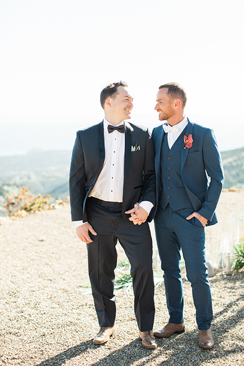 Los angeles same sex outdoor wedding at malibu solstice canyon groom navy shawl lapel tuxedo with a white dress shirt and black and white dot bow tie with groom blue notch lapel suit with a white dress shirt and white bow tie and orange floral boutonniere hugging and holding hands