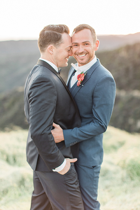 Los angeles same sex outdoor wedding at malibu solstice canyon groom navy shawl lapel tuxedo with a white dress shirt and black and white dot bow tie with groom blue notch lapel suit with a white dress shirt and white bow tie and orange floral boutonniere hugging and smiling close up