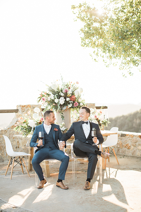 Los angeles same sex outdoor wedding at malibu solstice canyon groom navy shawl lapel tuxedo with a white dress shirt and black and white dot bow tie with groom blue notch lapel suit with a white dress shirt and white bow tie and orange floral boutonniere sitting at table holding wine smiling