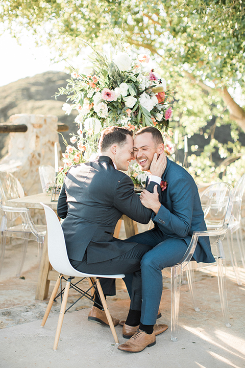 Los angeles same sex outdoor wedding at malibu solstice canyon groom navy shawl lapel tuxedo with a white dress shirt and black and white dot bow tie with groom blue notch lapel suit with a white dress shirt and white bow tie and orange floral boutonniere sitting at table hugging