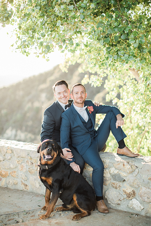 Los angeles same sex outdoor wedding at malibu solstice canyon groom navy shawl lapel tuxedo with a white dress shirt and black and white dot bow tie with groom blue notch lapel suit with a white dress shirt and white bow tie and orange floral boutonniere sitting on wall with dog front view