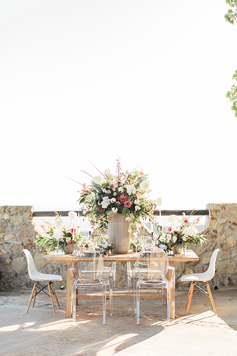 Los angeles same sex wedding at malibu solstice canyon table set up light brown wood table with white chairs and white and green flower centerpiece decor with white candles in glass vases and clear glass plates wedding photo idea side view