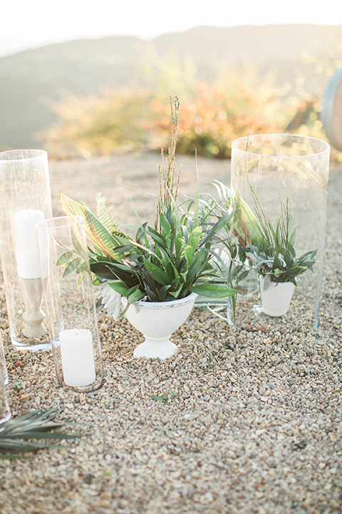 Los angeles same sex wedding at malibu solstice canyon table set up light brown wood table with white chairs and white and green flower centerpiece decor with white candles in glass vases and clear glass plates wedding photo idea