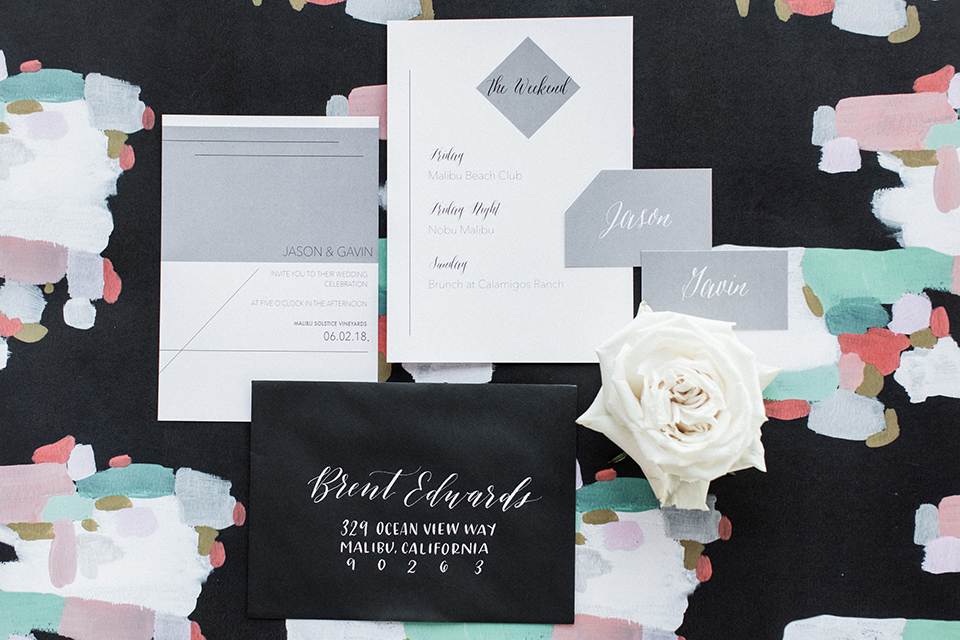 Los angeles same sex outdoor wedding at malibu solstice canyon wedding invitations black envelope with calligraphy writing and white invitations with grey decor on white floral background wedding photo idea for invitations