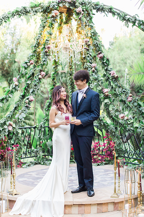 Los angeles outdoor wedding at eden gardens bride form fitting gown with draping detail and open back design with thin straps and groom navy blue shawl lapel tuxedo with a matching vest and white dress shirt with a black and white gingham plaid bow tie and pink floral boutonniere standing by ceremony altar holding drinks and hugging