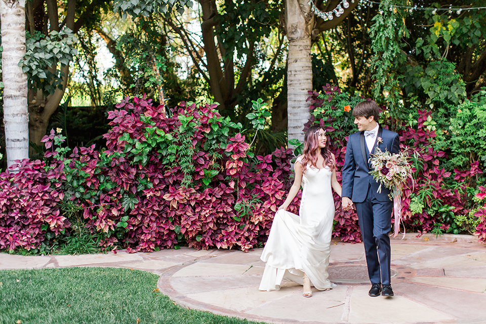 Los angeles outdoor wedding at eden gardens bride form fitting gown with draping detail and open back design with thin straps and groom navy blue shawl lapel tuxedo with a matching vest and white dress shirt with a black and white gingham plaid bow tie and pink floral boutonniere walking and holding hands groom holding green and pink floral bridal bouquet with ribbon decor