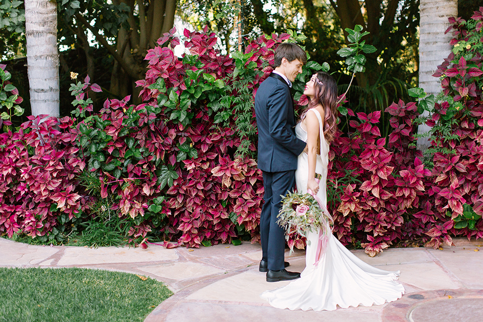 Los angeles outdoor wedding at eden gardens bride form fitting gown with draping detail and open back design with thin straps and groom navy blue shawl lapel tuxedo with a matching vest and white dress shirt with a black and white gingham plaid bow tie and pink floral boutonniere standing and hugging side view bride holding green and pink floral bridal bouquet with ribbon decor