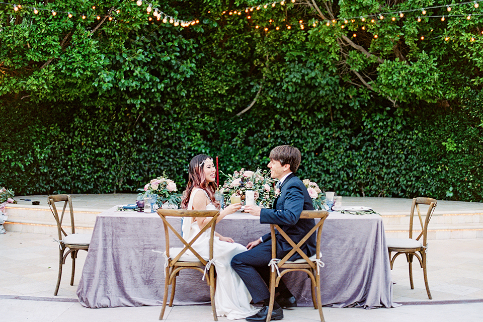Los angeles outdoor wedding at eden gardens bride form fitting gown with draping detail and open back design with thin straps and groom navy blue shawl lapel tuxedo with a matching vest and white dress shirt with a black and white gingham plaid bow tie and pink floral boutonniere sitting at table holding drinks