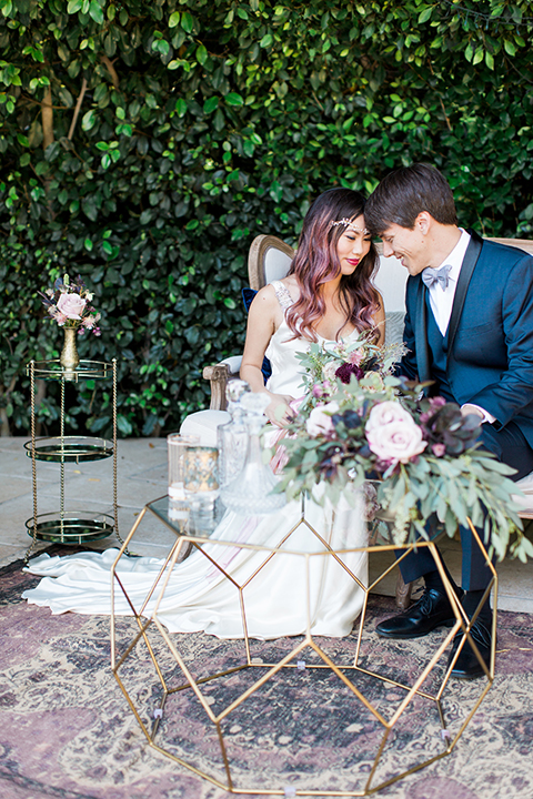 Los angeles outdoor wedding at eden gardens bride form fitting gown with draping detail and open back design with thin straps and groom navy blue shawl lapel tuxedo with a matching vest and white dress shirt with a black and white gingham plaid bow tie and pink floral boutonniere sitting on couch touching heads