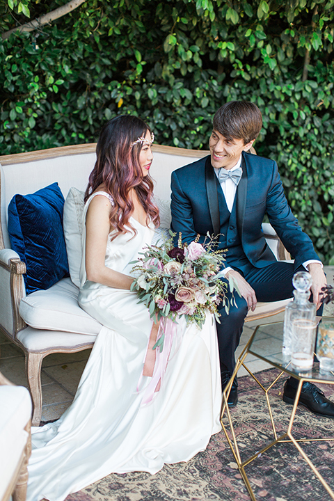 Los angeles outdoor wedding at eden gardens bride form fitting gown with draping detail and open back design with thin straps and groom navy blue shawl lapel tuxedo with a matching vest and white dress shirt with a black and white gingham plaid bow tie and pink floral boutonniere sitting on couch smiling bride holding green and pink floral bridal bouquet with ribbon decor