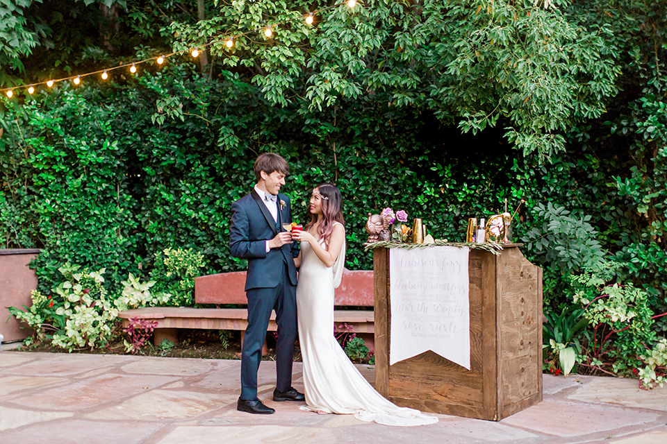 Los angeles outdoor wedding at eden gardens bride form fitting gown with draping detail and open back design with thin straps and groom navy blue shawl lapel tuxedo with a matching vest and white dress shirt with a black and white gingham plaid bow tie and pink floral boutonniere standing by bench and bar holding drinks and hugging