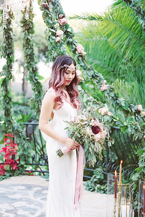 Los angeles outdoor wedding at eden gardens bride form fitting gown with draping detail and open back design with thin straps holding green and pink floral bridal bouquet with ribbon decor close up front view