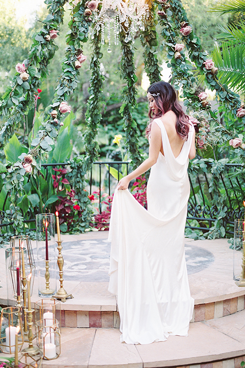 Los angeles outdoor wedding at eden gardens bride form fitting gown with draping detail and open back design with thin straps holding green and pink floral bridal bouquet with ribbon decor holding dress back view