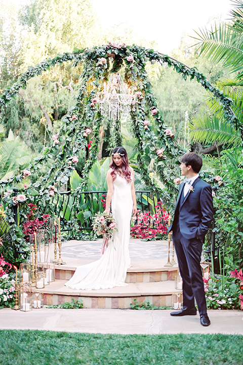 Los angeles outdoor wedding at eden gardens bride form fitting gown with draping detail and open back design with thin straps and groom navy blue shawl lapel tuxedo with a matching vest and white dress shirt with a black and white gingham plaid bow tie and pink floral boutonniere standing in ceremony area with floral altar and decor bride holding green and pink floral bridal bouquet with ribbon decor
