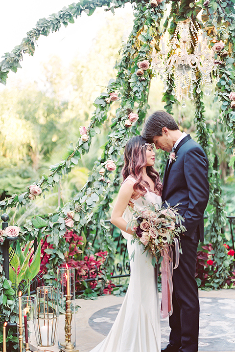 Los angeles outdoor wedding at eden gardens bride form fitting gown with draping detail and open back design with thin straps and groom navy blue shawl lapel tuxedo with a matching vest and white dress shirt with a black and white gingham plaid bow tie and pink floral boutonniere standing in ceremony floral altar hugging and touching heads close up bride holding green and pink floral bridal bouquet with ribbon decor