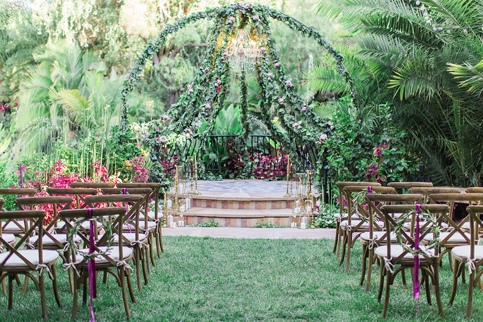 Los angeles outdoor wedding at eden gardens ceremony set up on grass with brown rustic chairs and greenery floral designs on altar with crystal chandelier and pink floral designs wedding photo idea for ceremony set up