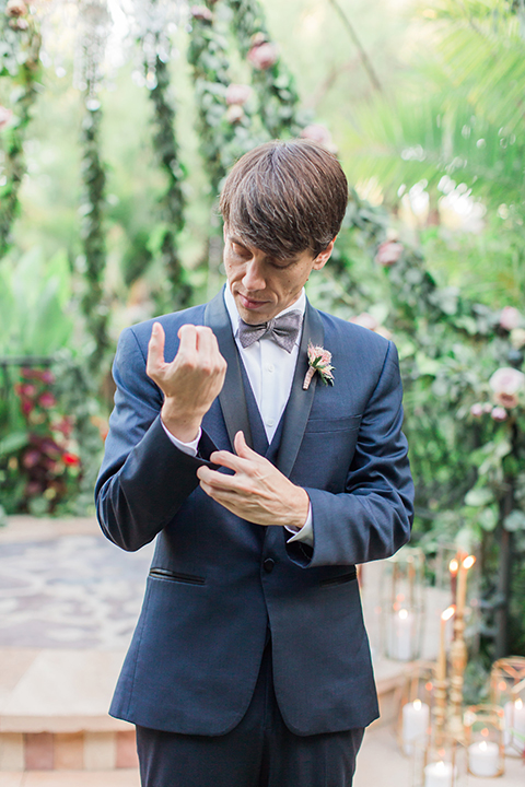Los angeles outdoor wedding at eden gardens groom navy shawl lapel tuxedo with a matching vest and white dress shirt with a black and white gingham plaid bow tie and pink floral boutonniere holding sleeve front view