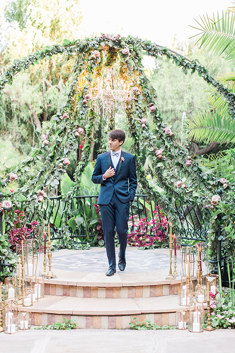 Los angeles outdoor wedding at eden gardens groom navy shawl lapel tuxedo with a matching vest and white dress shirt with a black and white gingham plaid bow tie and pink floral boutonniere standing by altar ceremony set up holding coat