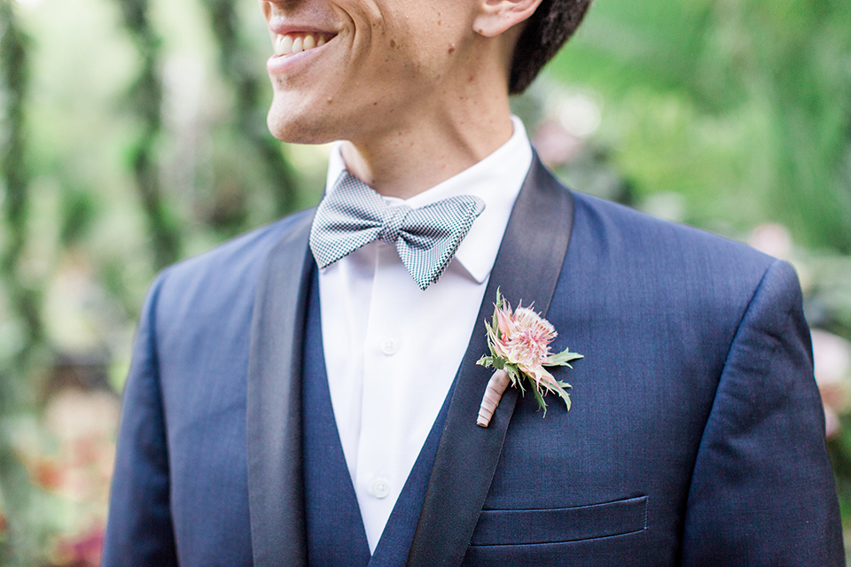 Los angeles outdoor wedding at eden gardens groom navy shawl lapel tuxedo with a matching vest and white dress shirt with a black and white gingham plaid bow tie and pink floral boutonniere close up on boutonniere