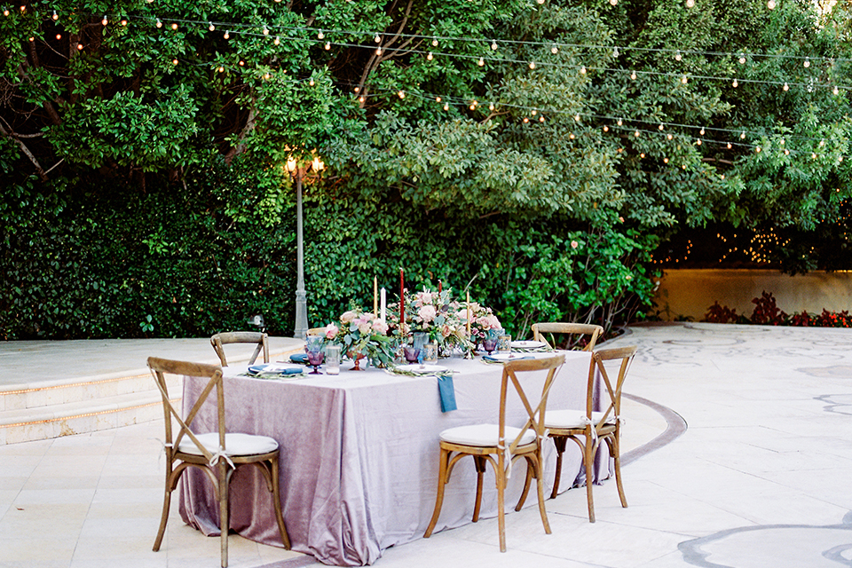 Los angeles outdoor wedding at eden gardens table set up with light grey table linen and white place setting with greenery and pink flower centerpiece decor and blue linen napkin with tall white and red candle decor and brown wood rustic chairs