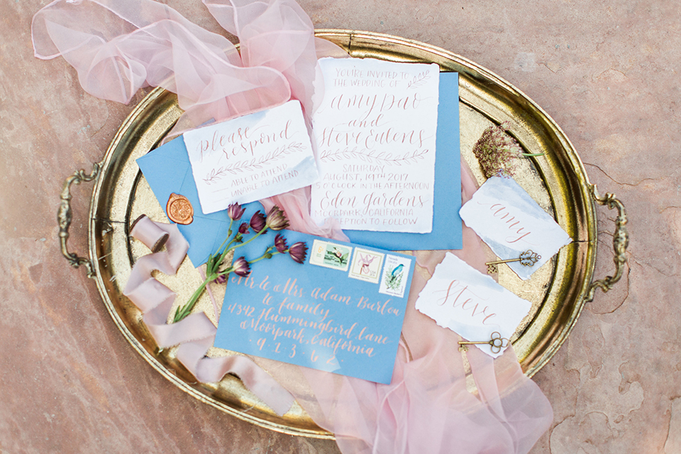 Los angeles outdoor wedding at eden gardens wedding invitations gold tray with white and blue invitations with blue envelopes and pink tulle decor wedding photo idea for invitations