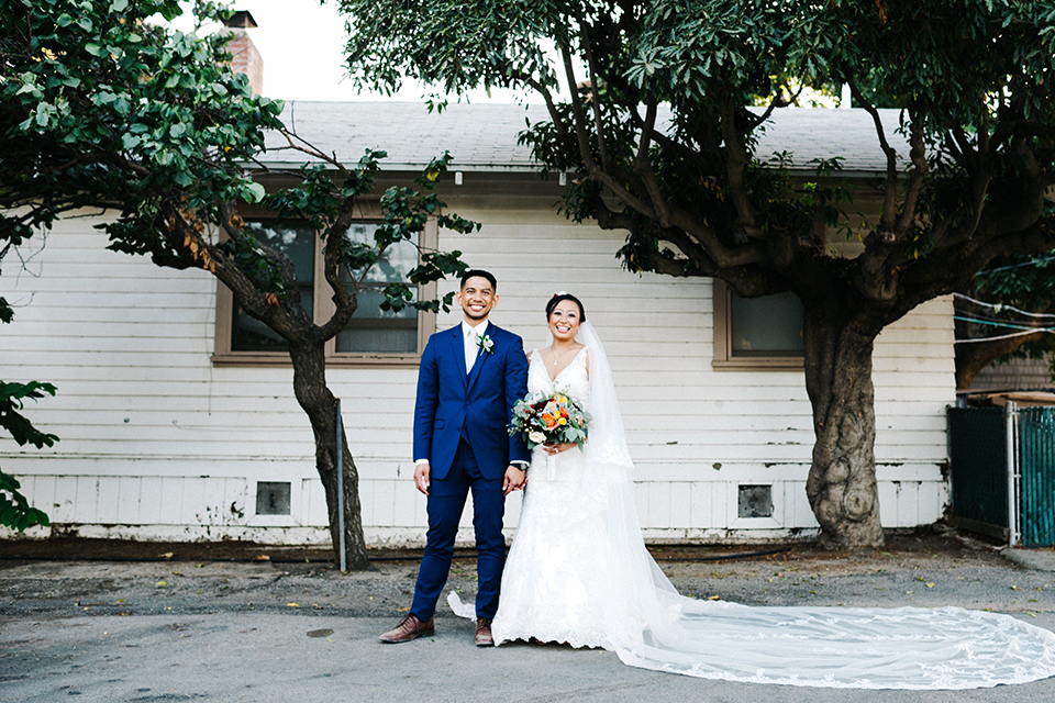 San diego autumn inspired outdoor wedding at limoneira ranch bride form fitting lace gown with straps and a v neckline with open back design and long veil with groom cobalt notch lapel suit by allure men with a matching vest and white dress shirt with a long white tie and white floral boutonniere holding hands and bride holding red and green floral bridal bouquet