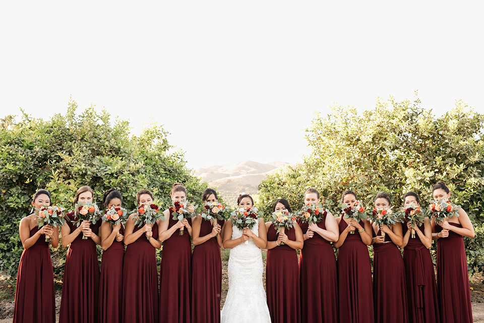 San diego autumn inspired outdoor wedding at limoneira ranch bride form fitting lace gown with straps and a v neckline with open back design and long veil holding green and dark red floral bridal bouquet standing with bridesmaids long burgundy dresses holding floral bouquets close to face