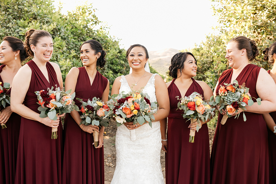 San diego autumn inspired outdoor wedding at limoneira ranch bride form fitting lace gown with straps and a v neckline with open back design and long veil holding green and dark red floral bridal bouquet standing with bridesmaids long burgundy dresses holding floral bouquets and smiling