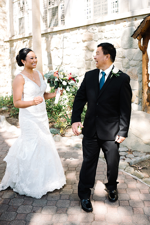 San diego autumn inspired outdoor wedding at limoneira ranch bride form fitting lace gown with straps and a v neckline with open back design and long veil holding green and dark red floral bridal bouquet standing with dad after first look navy blue suit with long cobalt blue tie smiling