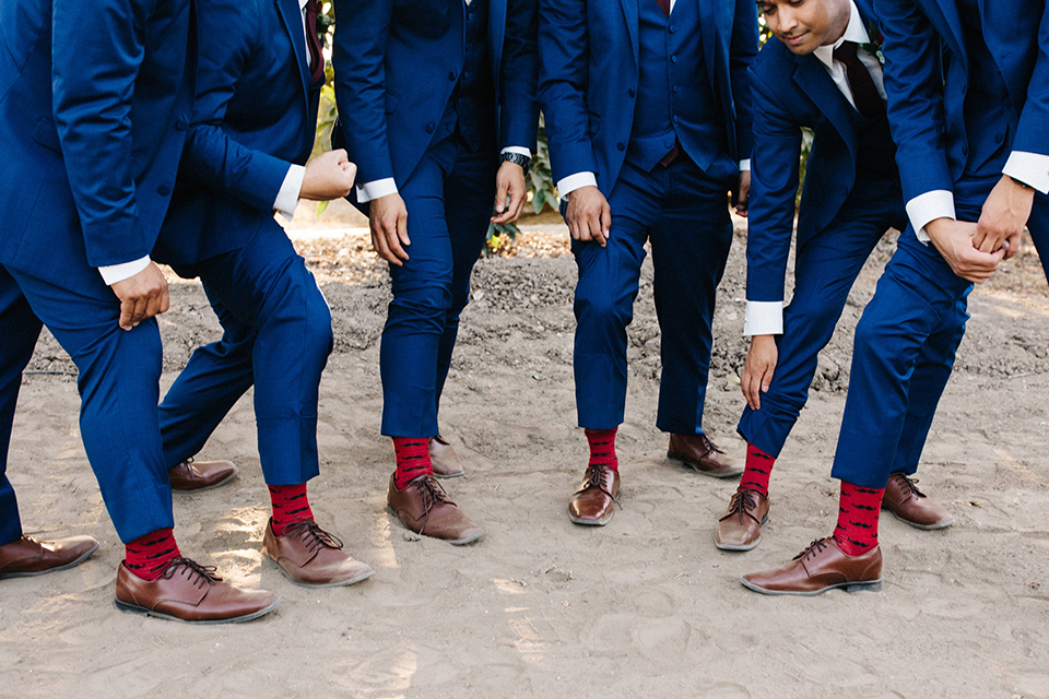 San diego autumn inspired outdoor wedding at limoneira ranch groom cobalt blue notch lapel suit with a matching vest and white dress shirt with a long white tie and white floral boutonniere standing with groomsmen cobalt blue suits close up on brown shoes with red mustache socks fun wedding photo idea for groomsmen