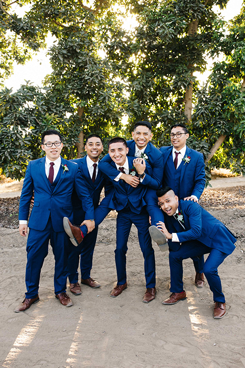San diego autumn inspired outdoor wedding at limoneira ranch groom cobalt blue notch lapel suit with a matching vest and white dress shirt with a long white tie and white floral boutonniere standing with groomsmen cobalt blue suits with long burgundy ties and burgundy floral boutonnieres smiling