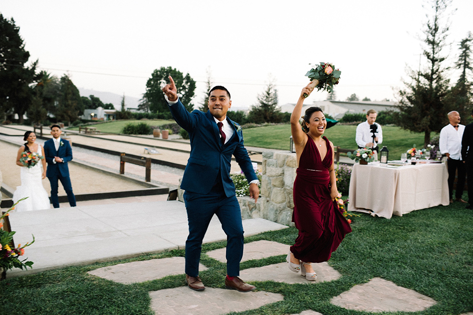 San diego autumn inspired outdoor wedding at limoneira ranch reception wedding party entrance bridesmaid long burgundy dress with red and green floral bouquet walking in with groomsman cobalt blue suit with a long burgundy tie and burgundy floral boutonniere