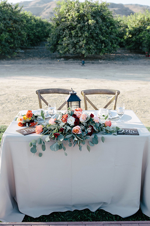 San diego autumn inspired outdoor wedding at limoneira ranch table set up light blue table linen with light orange and green flower centerpiece decor with light brown wooden rustic chairs and lantern and candle decor