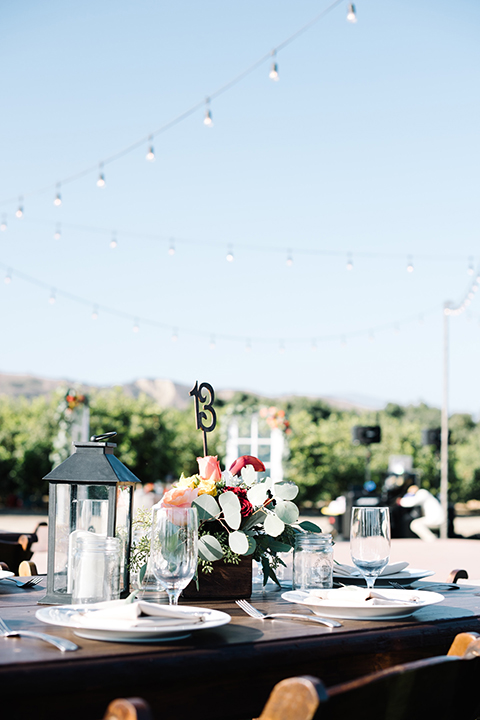 San diego autumn inspired outdoor wedding at limoneira ranch table set up light blue table linen with light orange and green flower centerpiece decor with light brown wooden rustic chairs and lantern and candle decor with table number in flowers